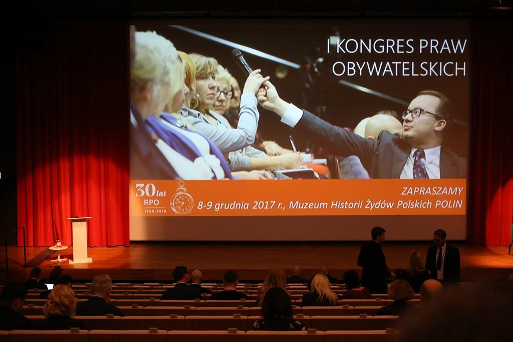 Kobieta na scenie, na ekranie zdjęcie RPO Bodnara dającego mikrofon ludziom na widowni