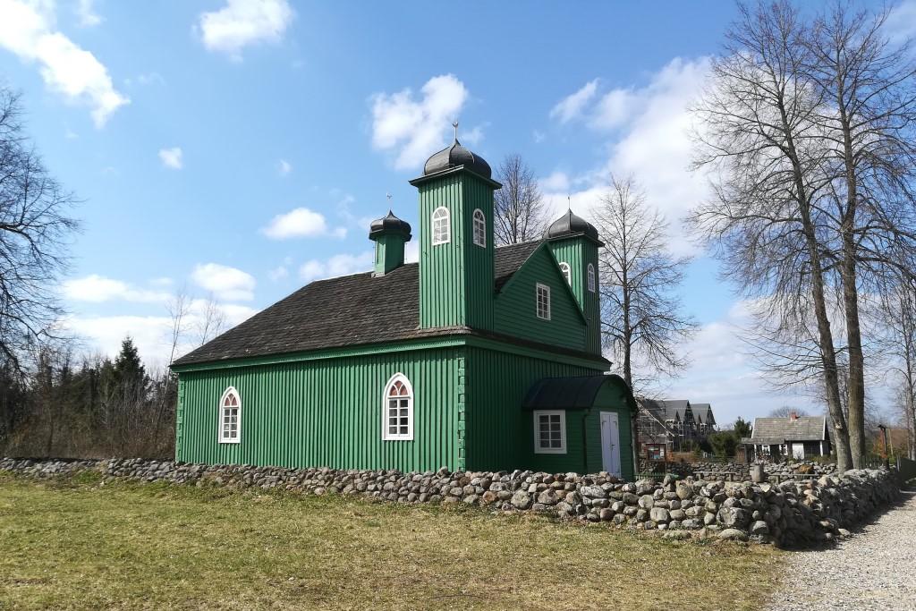 Zielony budynek drewniany z półksiężycem na wieżyczkach