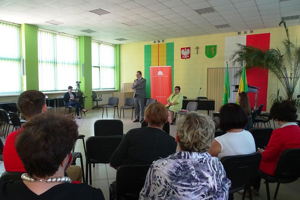 Ludzie na sali, mężczyzna w szarym garniturze stoi, w tle - logo RPO