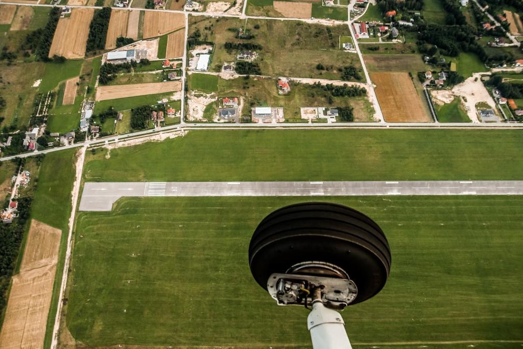Koło samolotu i widok na ziemię - pola i domy