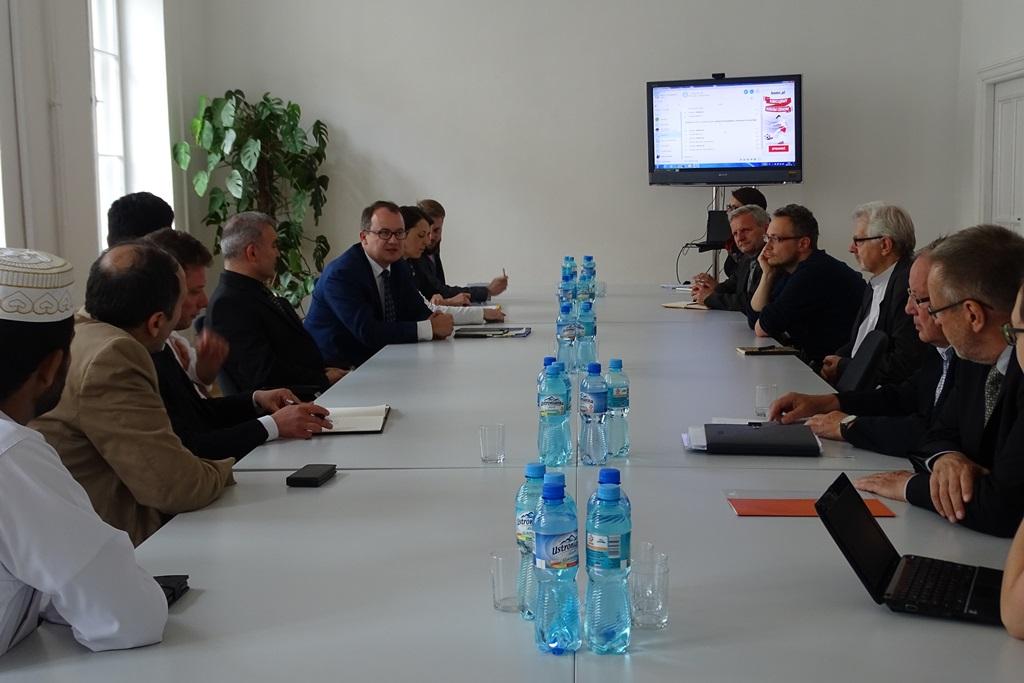 Zdjęcie: widok na stół, przy którym z dwóch stron siedzą ludzie. W głębi - monitor telewizujny