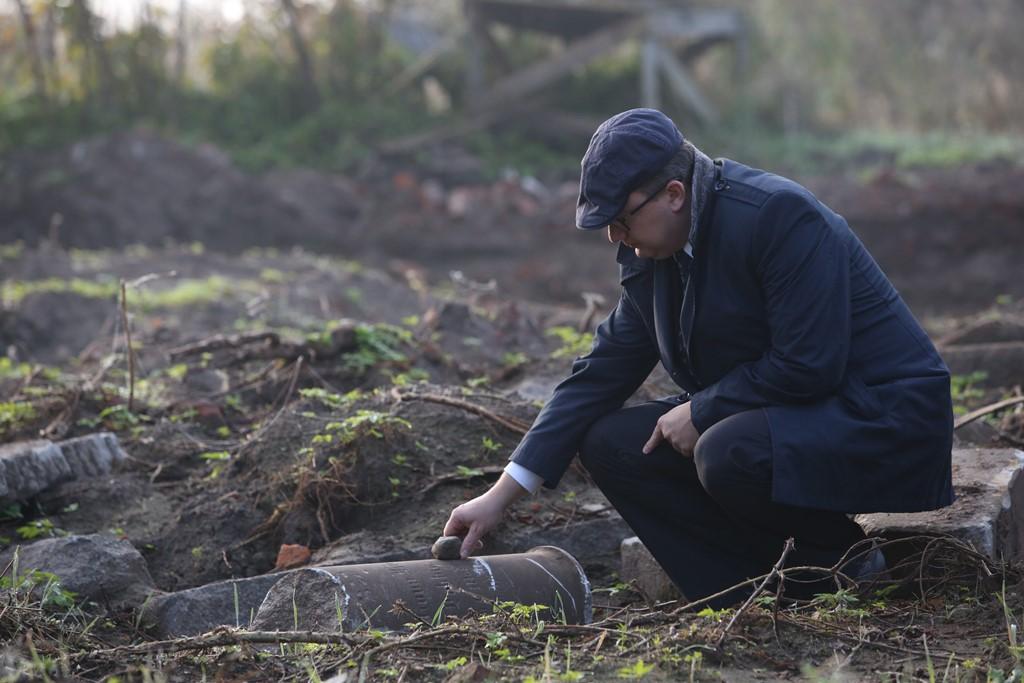 Mężczyzna w czapce kładzie kamień na zwalonych tablicach nagrobnych