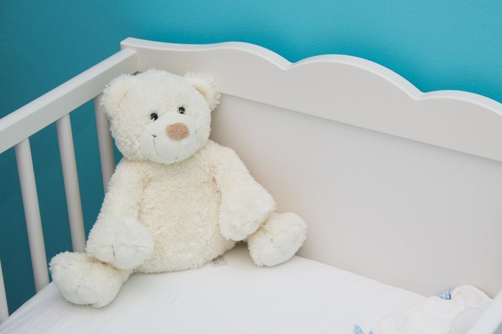 Miś w pustym dziecięcym łóżeczku