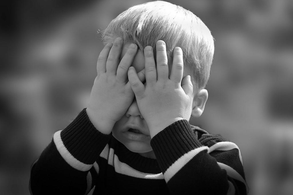 Dziecko zasłania twarz rączkami i myśli, że go nie ma
