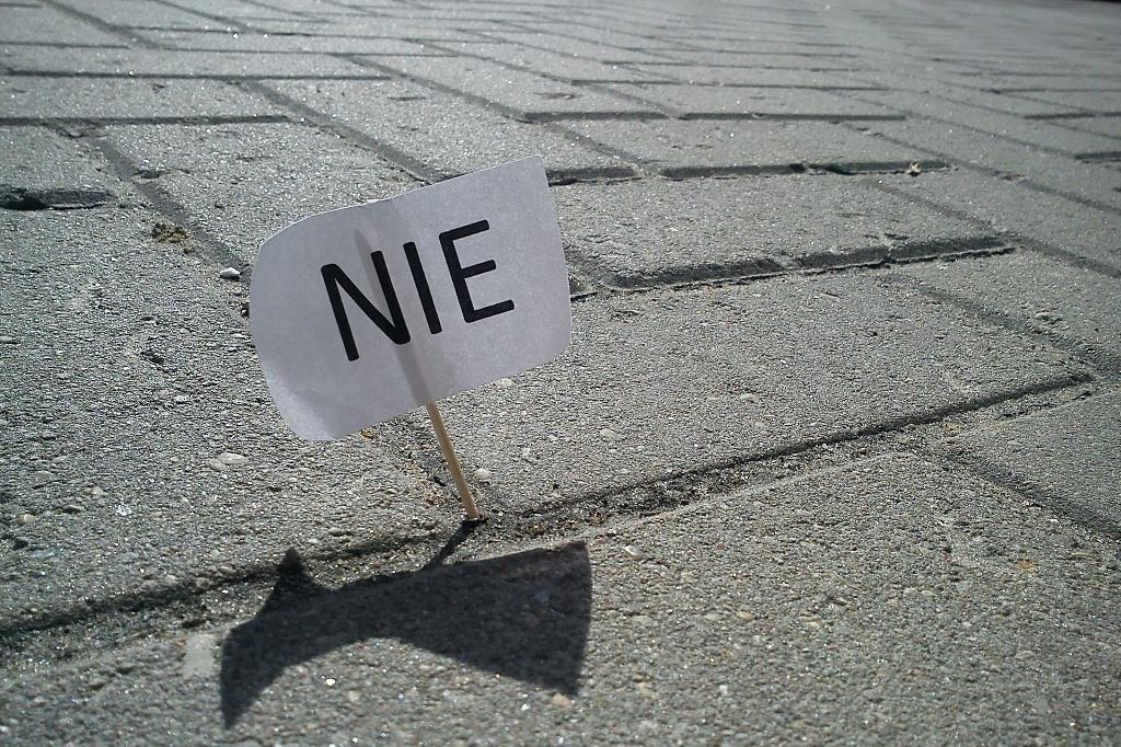 Tabliczka z napisem NIE zatknięta na chodniku