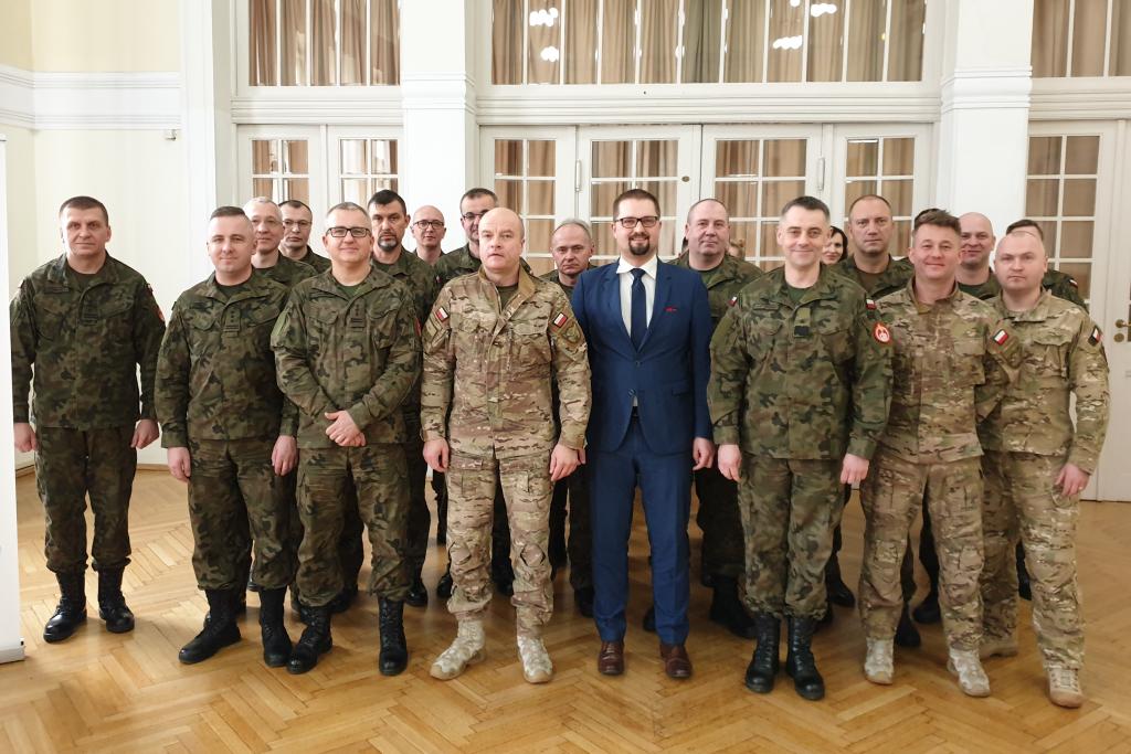 Zdjęcie grupowe - mężczyźni w polowych mundurach wojskowych i mężczyzna w garniturze