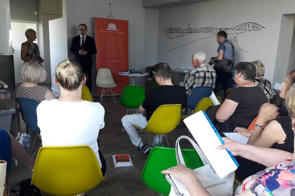 Ludzie na sali siedzą na kolorowych krzesłach