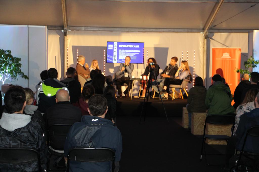 Paneliści  w głębi, ludzie w namiocie