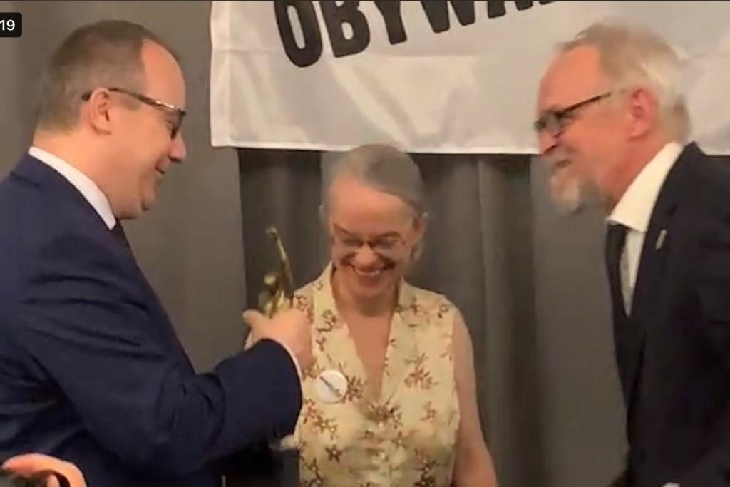 Mężczyzna i kobieta wręczają statuetkę mężczyżnie