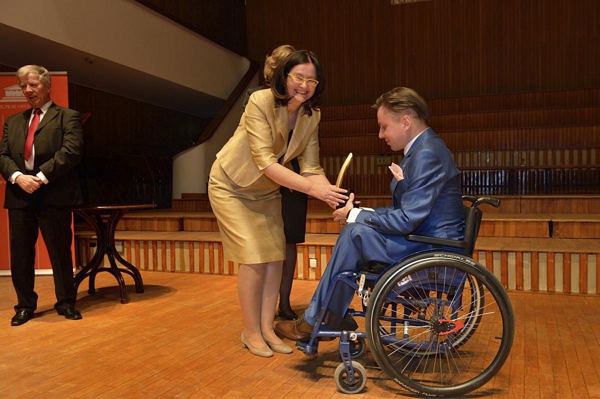 kobieta wręcza statuetkę mężczyźnie na wózku