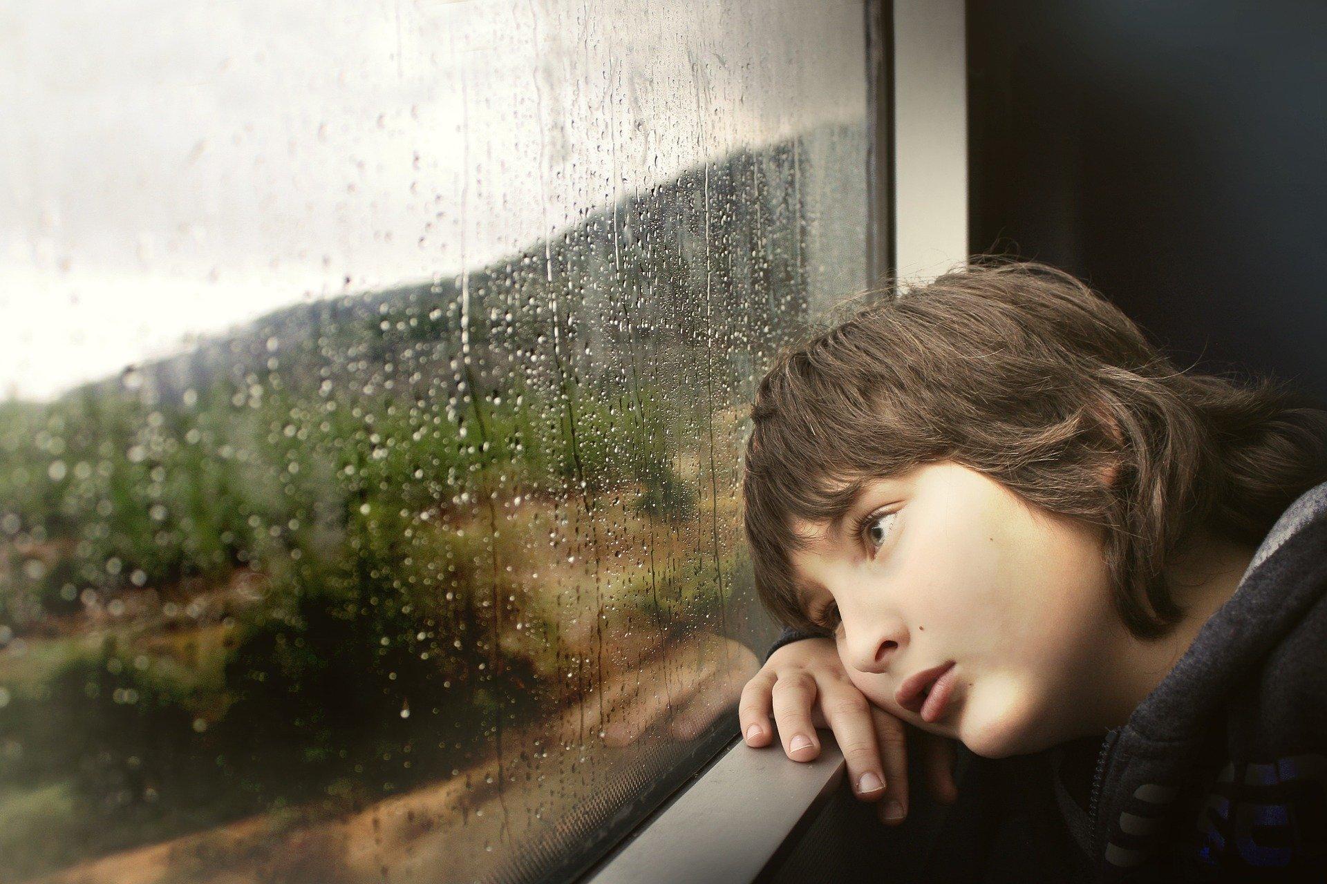 Zamyślony smutny chłopiec leżący na parapecie i wpatrujący się w deszcz za oknem.