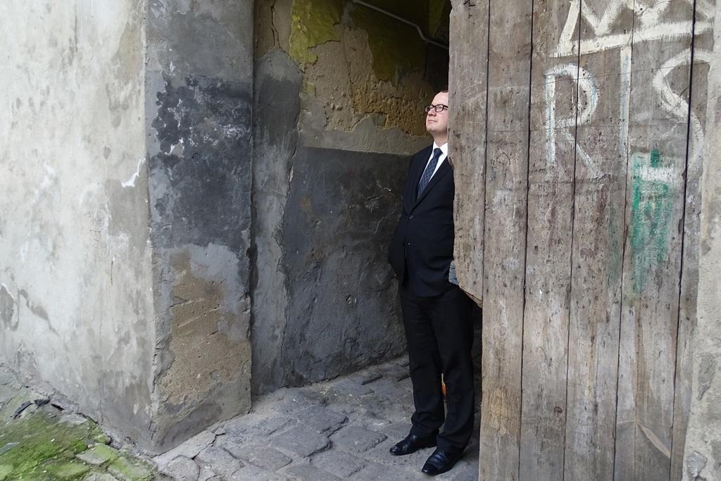 Mężczyzna stoi w bramie starej kamienicy