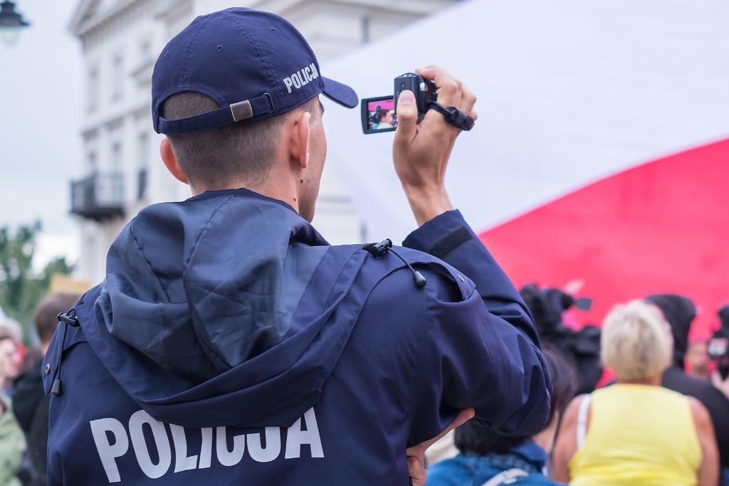 Policjant filmujący biało-czerwoną flagę