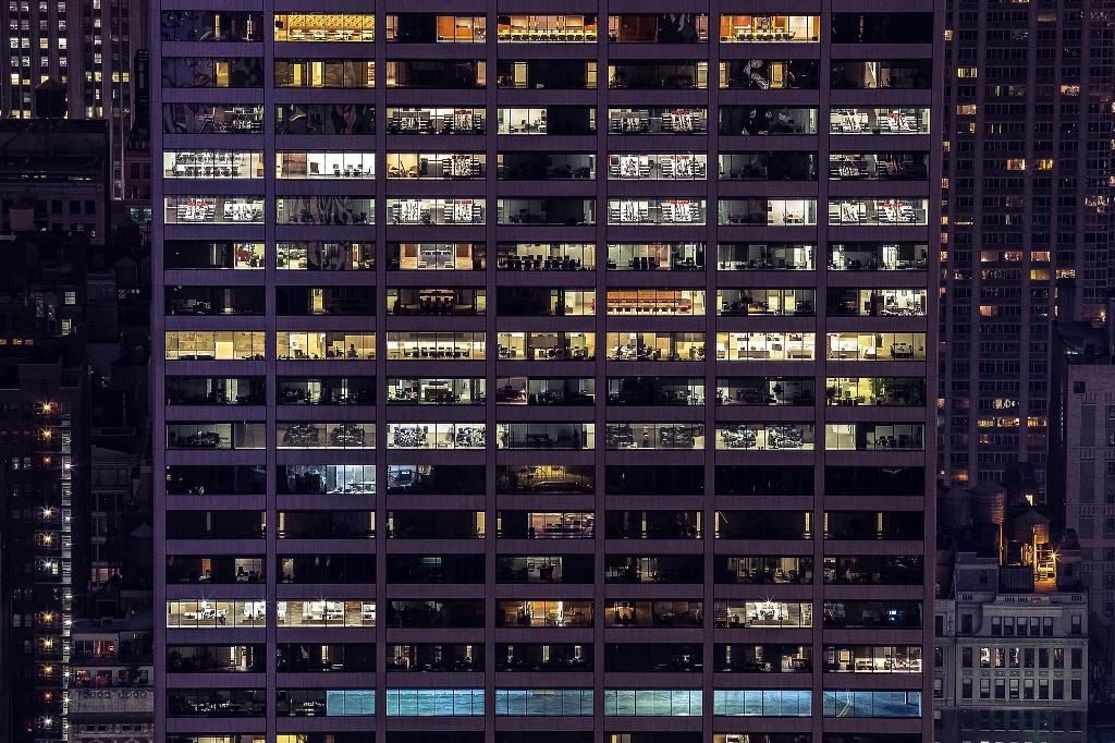 Oświetlony budynek biurowy, ludzie pracują