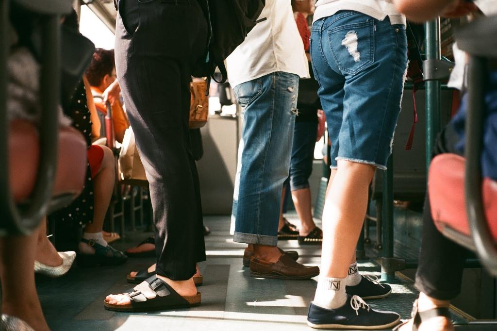 Sylwetki ludzi stojących w autobusie