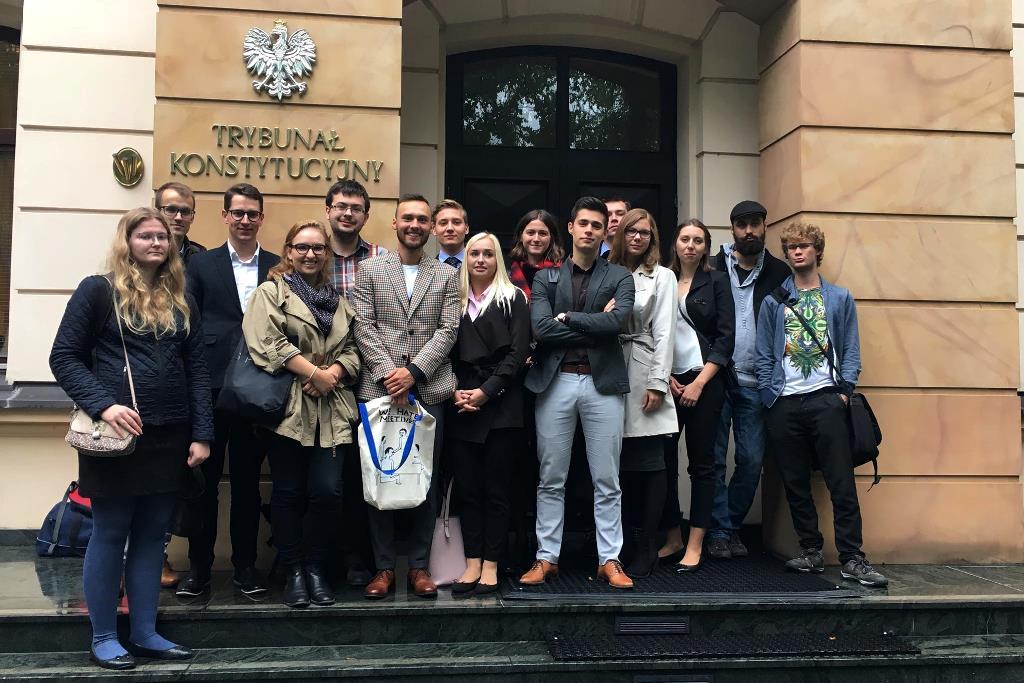 zdjęcie: kilkanaście osób stoi na schodach przy budynku z napisem: Trybunał Konstytucyjny