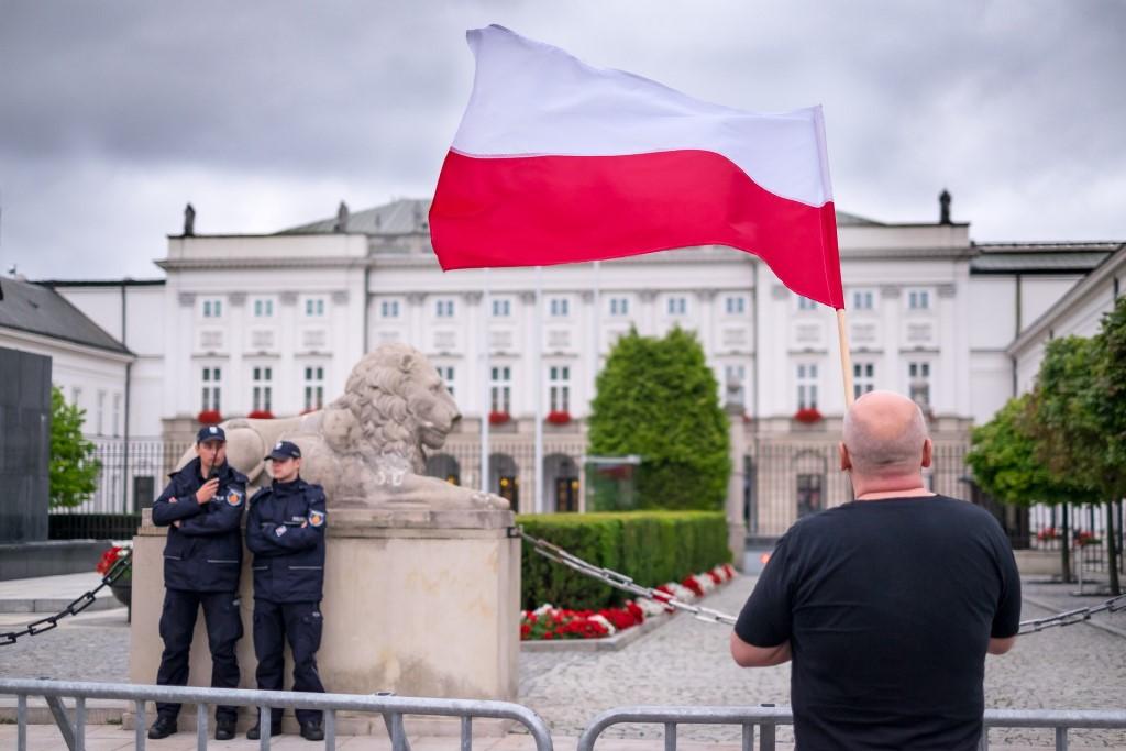 Mężczyzna z biało-czerwoną flagą przed białym budynkiem