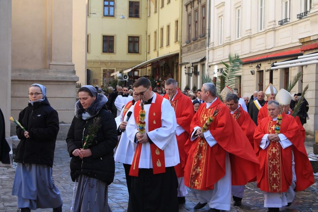 Procesja - zakonnice i księża w czerwonych szatach niosą palmy