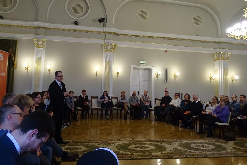 Zdjęcie: ludzie siedzą w kręgu, rzecznik stoi