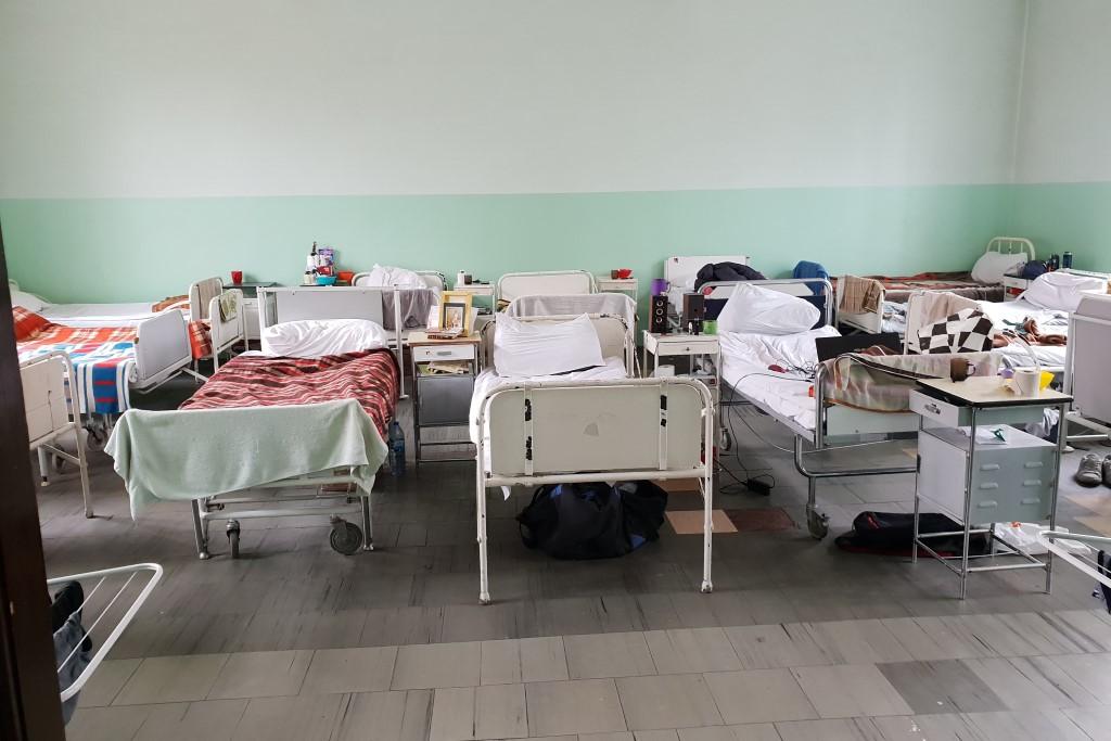 Łóżka szpitalne ustawione w dwuszeregu w dużej sali