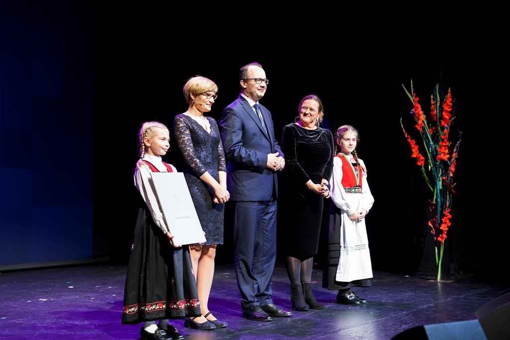 Troje dorosłych i dwie dziewczynki w norweskich strojach stoją na scenie