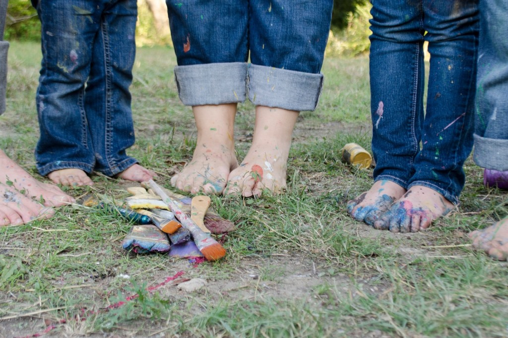 Zdjęcie dzieci  - widać tylko gole stopy na ziemi i kolorowe pędzle