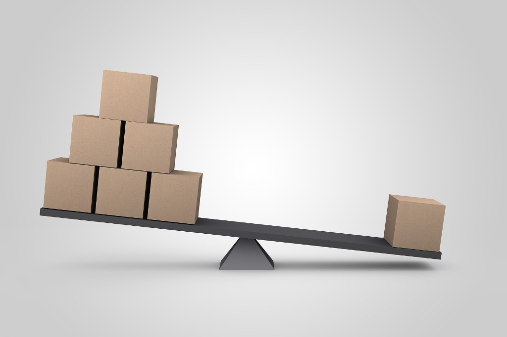 Symbol nierównowagi: jeden klocek przeważa na równoważni wiele takich samoch kloków