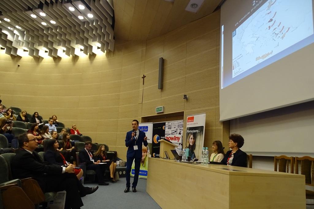 Zdjęcie: młody mężczyzna przedstawia prezentacje. Na ekranie mapa Polski ze strzałkami ze wschodu