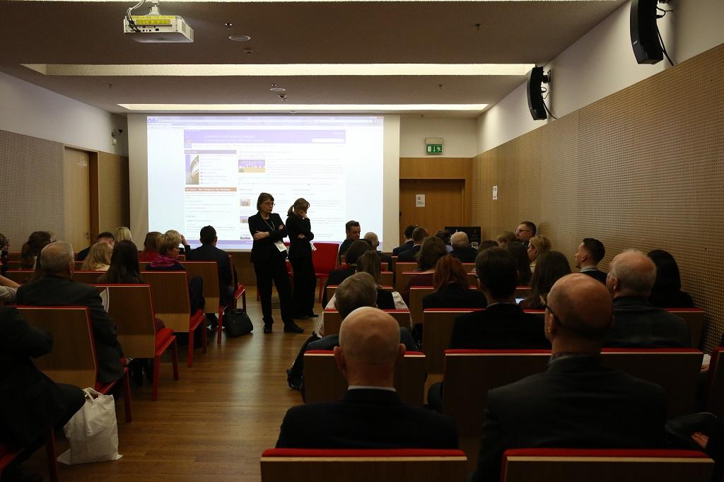 Sala konferencyjna pełna ludzi, czerwone krzesła