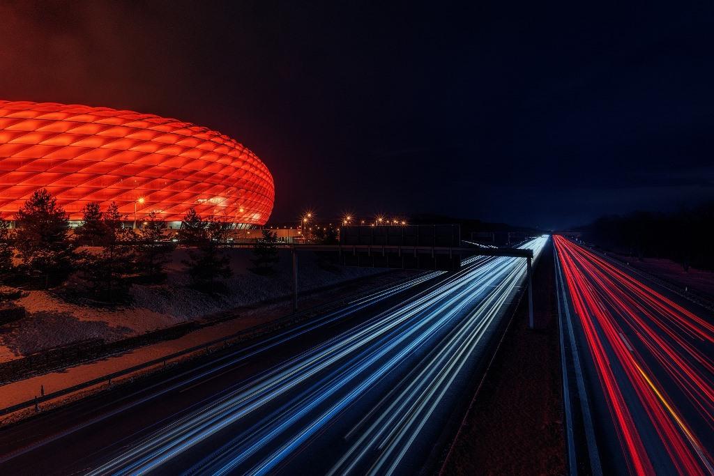 Samochody na szerokiej ulicy nocą, po lewej oświetlony na czerwono stadion piłkarski