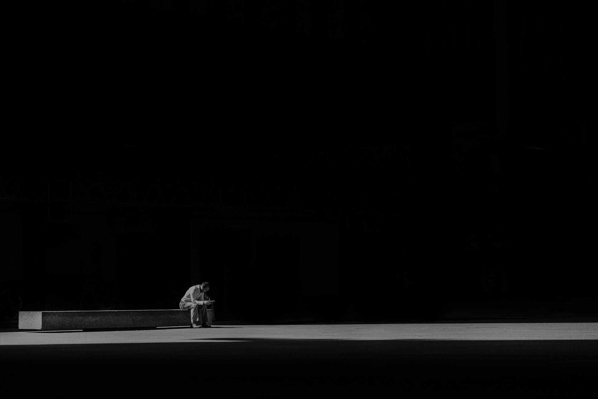 Samotny człowiek w ciemnościach siedzi na ławce