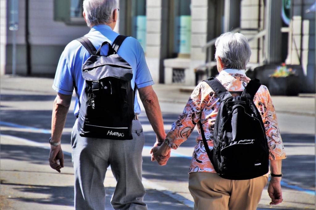 Dwoje starszych ludzi z plecakami idzie przez miasto trzymając się za ręce