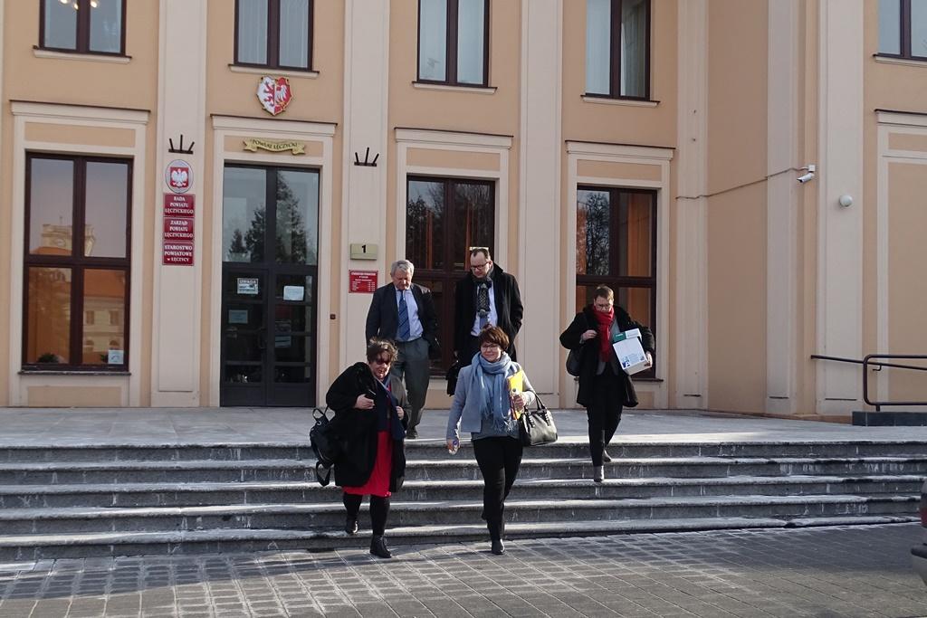 Grupa ludzi wychodzi z budynku