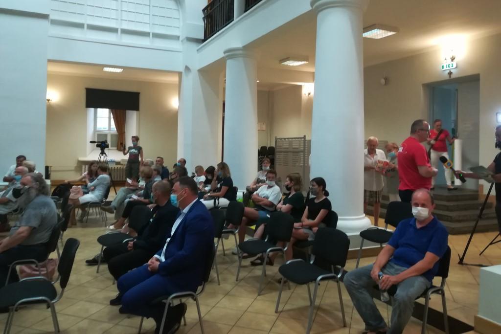 Ludzie na sali, z prawej mężczyzna w czerwonej koszulice udziela wywiadu