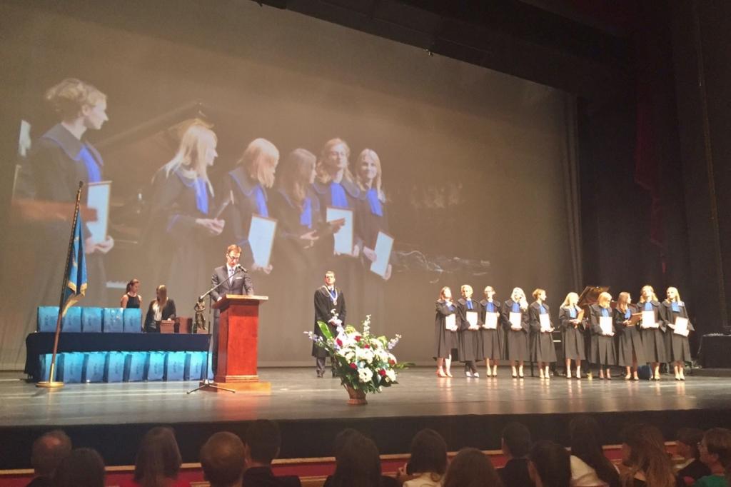 zdjęcie: grupa osób w togach z niebieskimi żabotami stoi na scenie za nimi widać duży telebim
