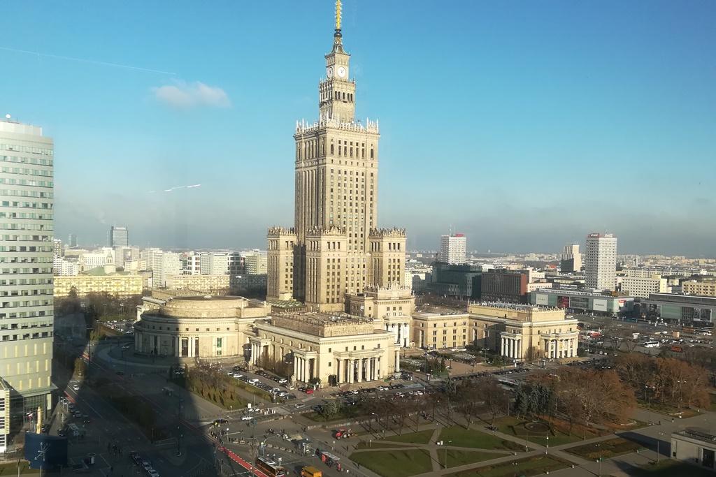 Widok z warszawskiego wieżowca a Pałac Kultury, na horyzoncie widać szarą mgłę na błękitnym niebie