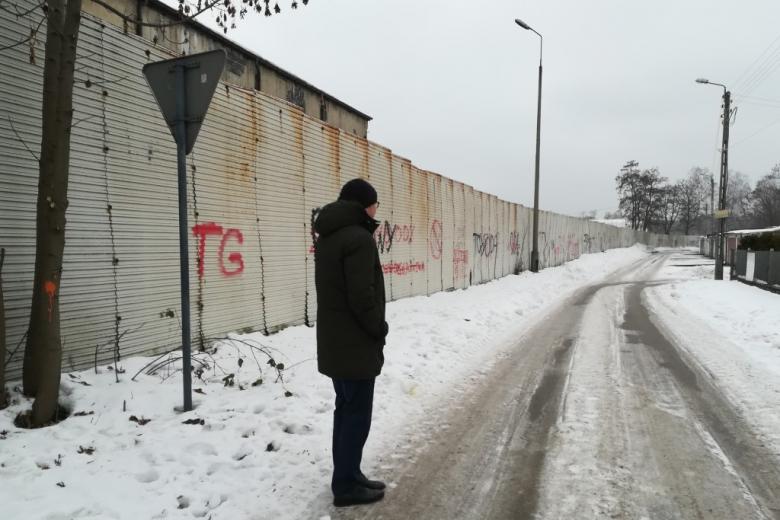 Mężczyzna na uliczce na osiedlu domków jednorodzinnych. Płot wzdłuż jezdni