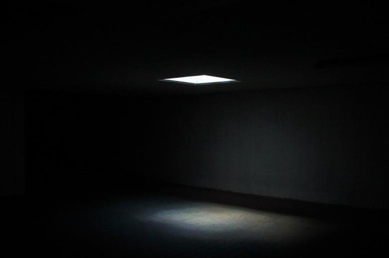 zdjęcie snopu światła padającego z góry w ciemnym pomieszczeniu