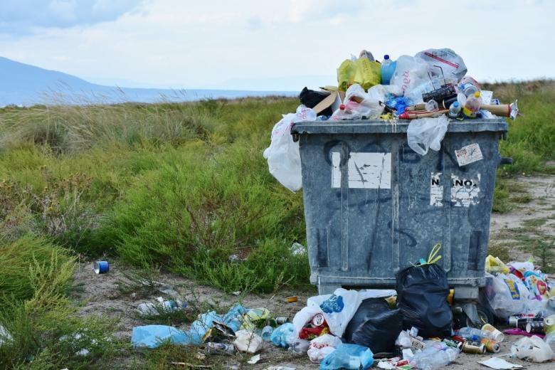 Kontener na śmieci, z którego wysypują się odpadki
