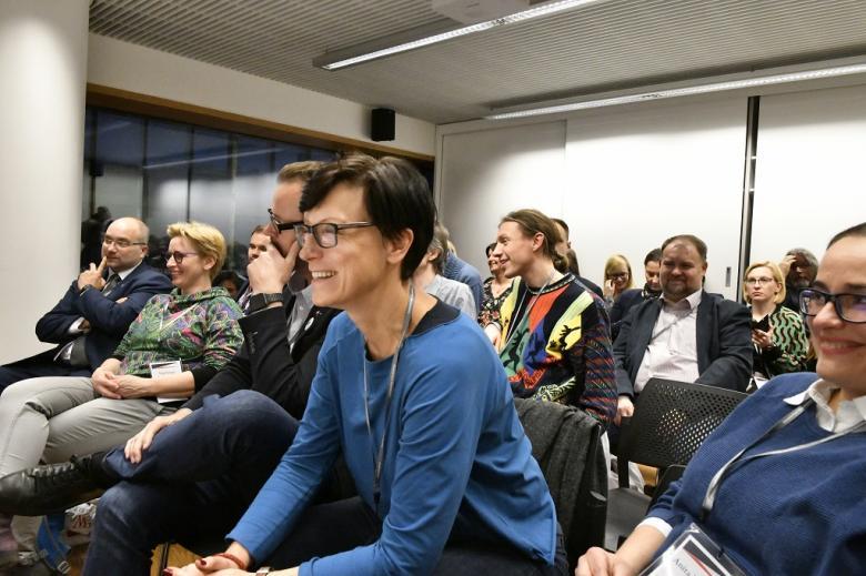 Uczestnicy panelu, na pierwszym planie uśmiechnięta kobieta w niebieskiej bluzie