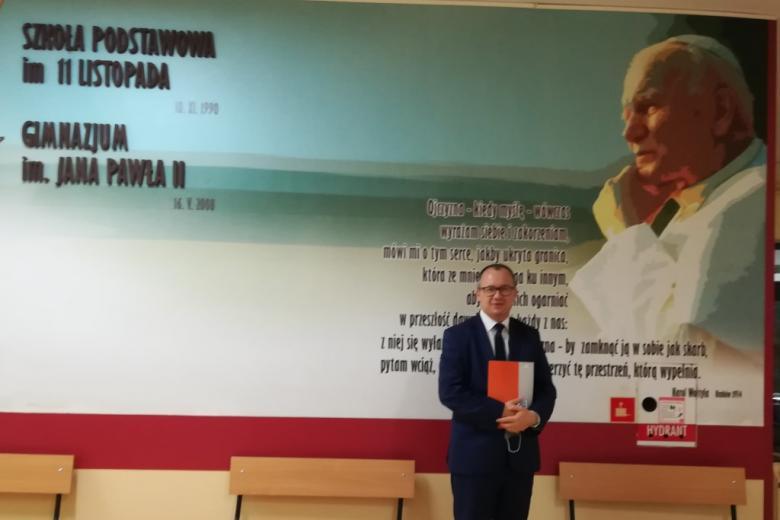 Mężczyzna przed tablicą, że szkoła podstawowa nosi imię 11 Listopada, a gimnazjum  - Jana Pawła II