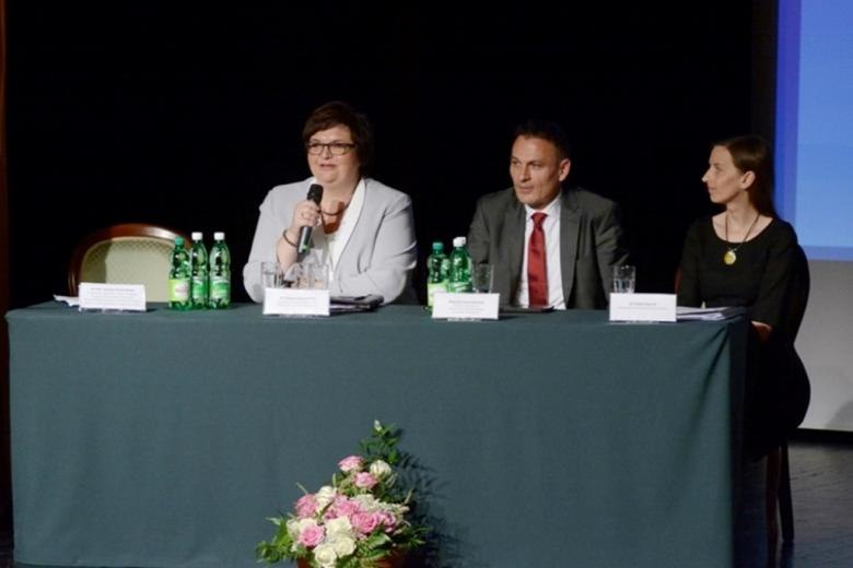 zdjęcie: za stołem przykrytym obrusem przed którym stoją kwiaty, siedzą dwie kobiety i mężczyzna pomiędzy nimi