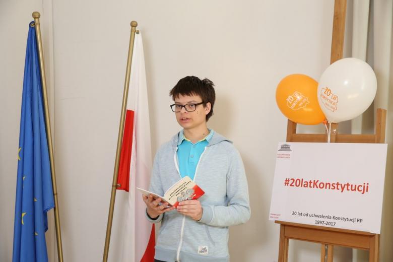 zdjęcie: młody chłopak stoi przy polskiej i unijnej fladze i trzyma w ręku Konstytucję
