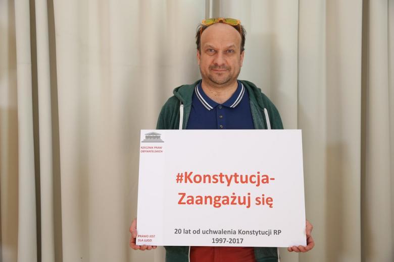 zdjęcie: mężczyznza stoi i trzma planszę z napisem: Konstytucja - zaangażuj się