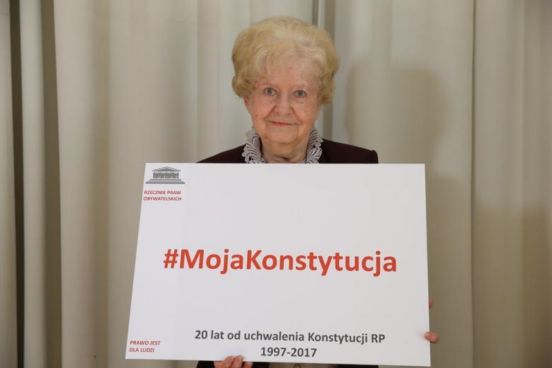zdjęcie: starsza pani trzyma tablicę z napisem: Moja Konstytucja