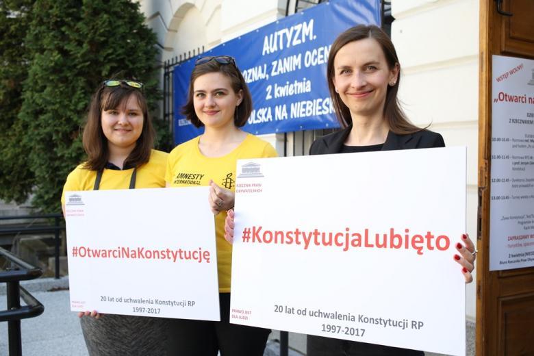 zdjęcie: trzykobiety stoją i trzymają plansze z napisami o konstytucji