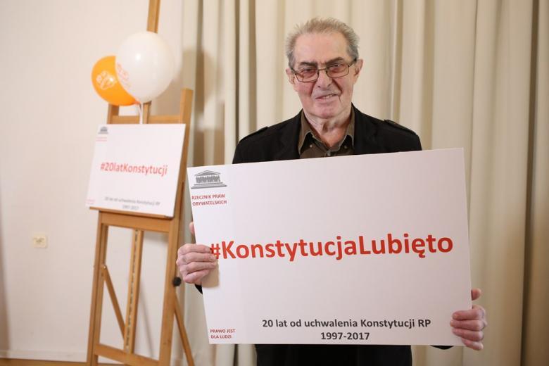 zdjęcie: mężczyzna trzyma planszę z napisem: Konstytucja Lubię To