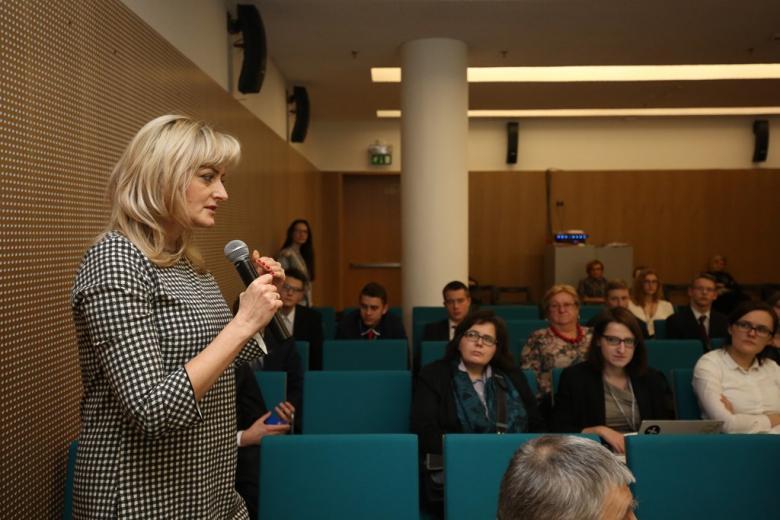 zdjęcie: kilka osob siedzi na sali, jedna z kobiet stoi i mówi do mikrofonu