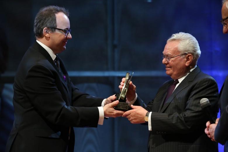 zdjęcie: mężczyzna wręcza drugiemu mężczyźnie statuetkę