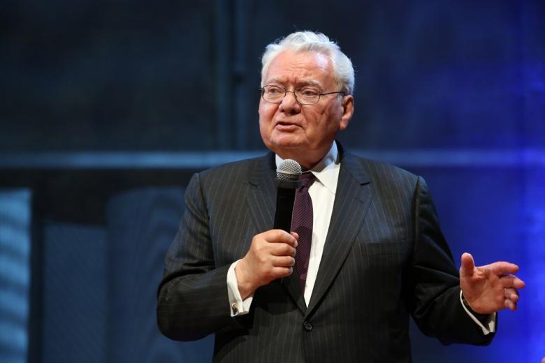 zdjęcie: mężczyzna stoi i mówi do mikrofonu gestykulując